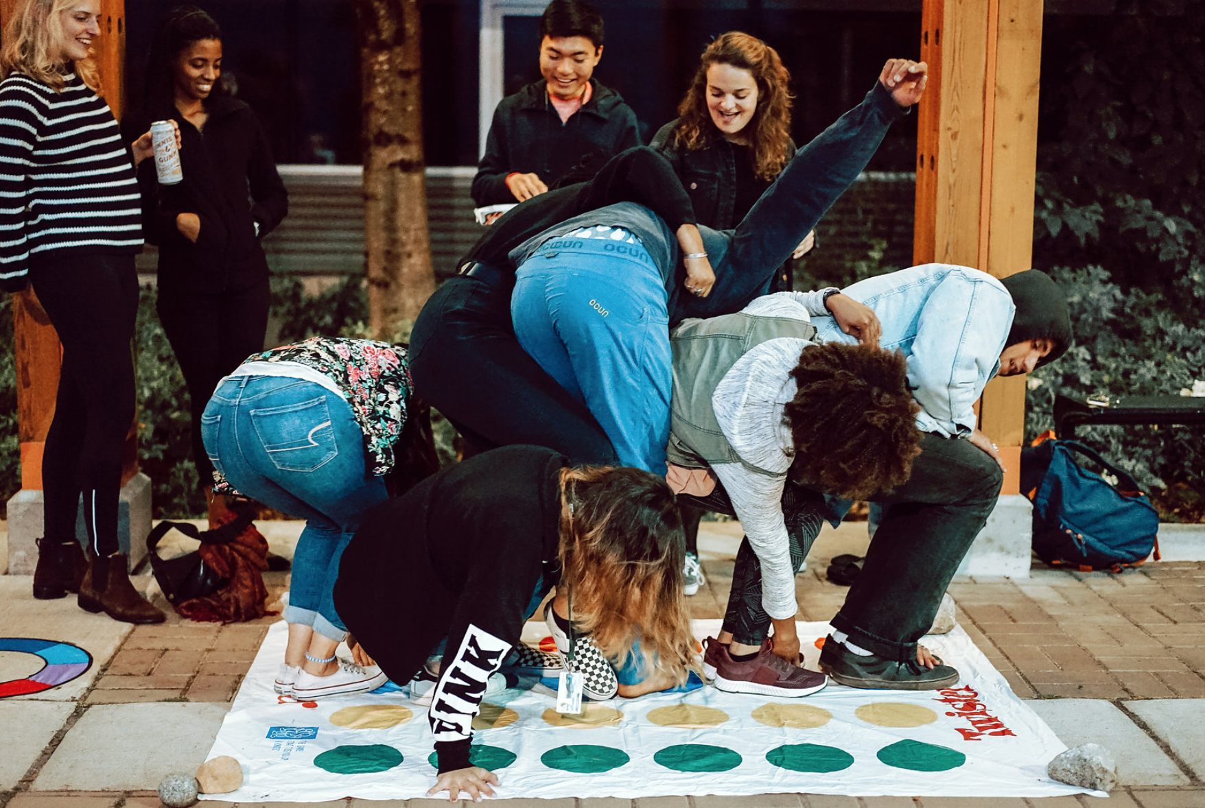 Image of a group of students outside of the library building playing the game Twister and having fun.